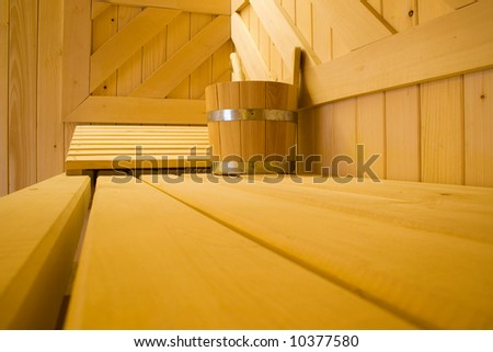 Bucket for water and pillow on bench in Finnish sauna. - stock photo