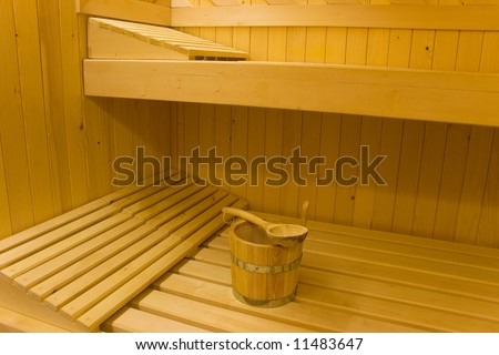 Bucket for water and pillows on benches in Finnish sauna. - stock photo