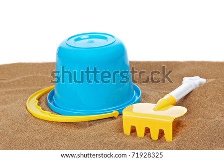 Bucket full and rake on the sand with copy space on a white background. Shallow depth of field - stock photo