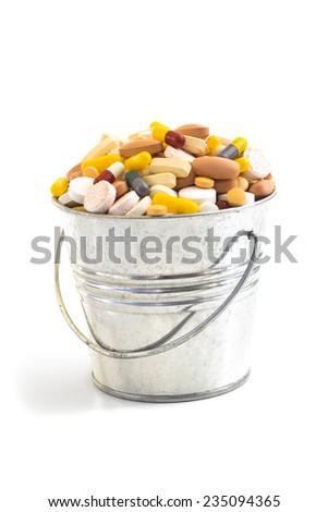 BUCKET FULL OF DRUGS 3 Bucket full of pills and capsules. - stock photo