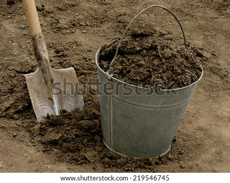 bucket full of soil with spade on dirt background - stock photo