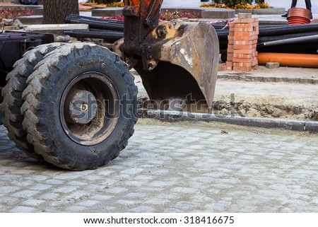 Bucket hydraulic excavator participates in the repair of the street - stock photo