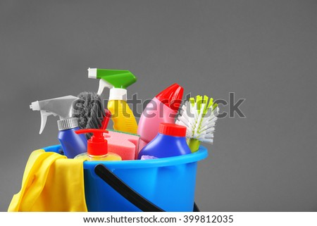 Bucket of cleaning supplies on a grey background