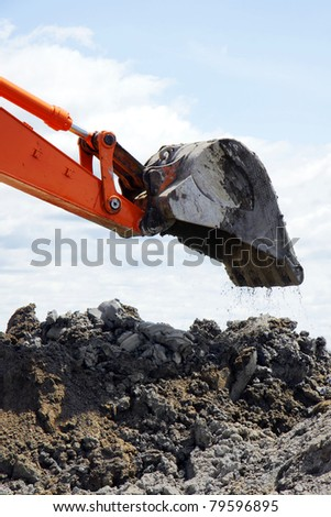 Bucket of orange mechanical digger dropping a scoop of clay soil on heap of dirt during major rural construction. - stock photo