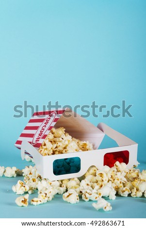 Bucket of popcorn against a blue background