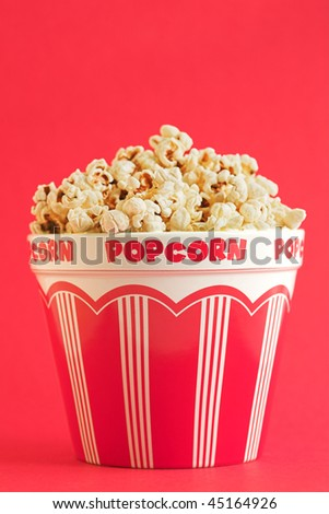 Bucket of popcorn on a red background - shallow dof - stock photo