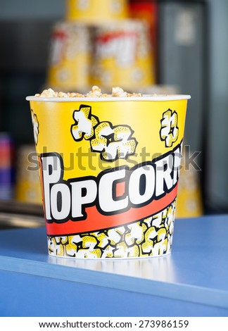 Bucket of popcorn on cinema concession counter - stock photo