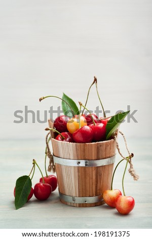 Bucket of red and yellow cherries on blue wooden background. Vertical - stock photo