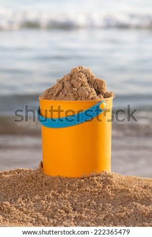 Bucket of sand on the beach - stock photo