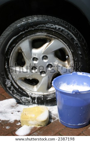 Bucket of soapy water by wheel of car - stock photo