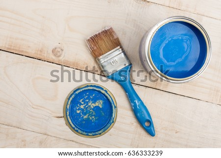 Bucket with blue color and a brush for painting on a wooden board.