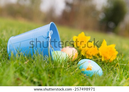 Bucket with chocolate easter eggs outdoor in the garden - stock photo