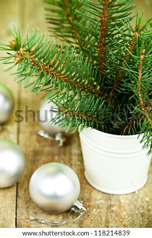 bucket with christmas fir tree and white decorations on a wooden board - stock photo