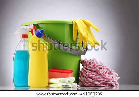 bucket with detergents and mop on the gray background