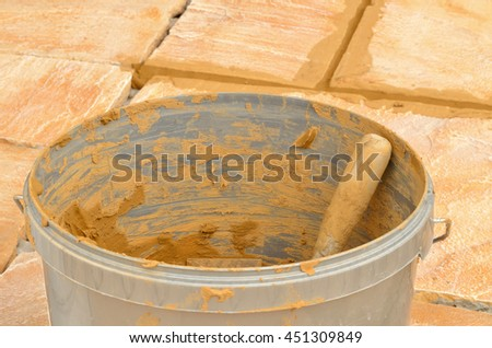 Bucket with grout on concrete outdoor tiles, sandstone colored paving on the terrace with brown not dry joints - stock photo