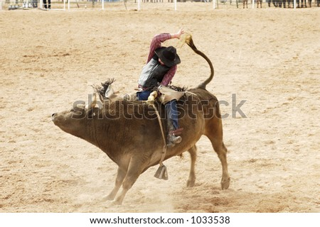 Bucking action during the bull rinding competition at a rodeo. - stock photo