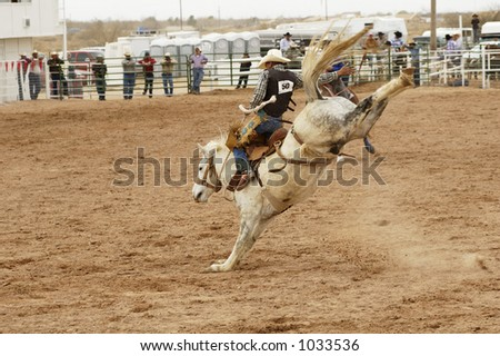 Bucking action during the saddle bronc riding competition at a rodeo. - stock photo