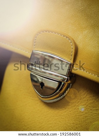 Buckle on a leather bag in the window. lens flare - stock photo