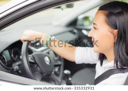 Buckled up woman driving with one hand on steering wheel
