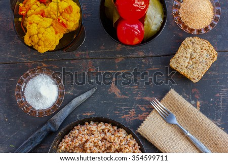 Buckwheat, corn bread, pickled tomatoes, broccoli and salt shakers on the old table. The concept of the winter vegetarian lunch in the village. Free space for text. Copy space - stock photo