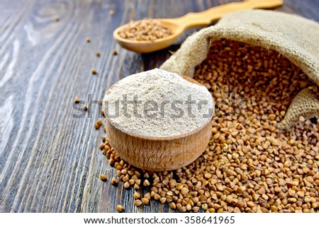 Buckwheat flour in a wooden bowl, buckwheat in a bag on a wooden boards background - stock photo