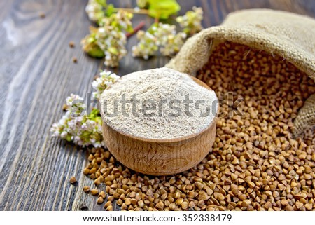 Buckwheat flour in a wooden bowl, buckwheat in the bag, buckwheat flower on the background of wooden boards - stock photo