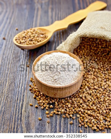 Buckwheat flour in a wooden bowl, grains in a bag on a dark wood board