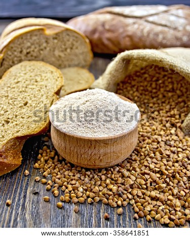 Buckwheat flour in a wooden bowl, grains in the bag, the bread slices on a wood boards background