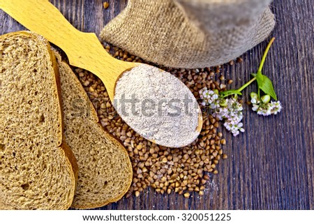 Buckwheat Flour in a wooden spoon, buckwheat in the bag, slices of bread, buckwheat flower on the background of wooden boards on top - stock photo