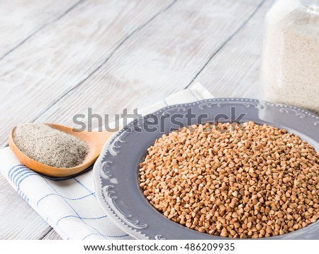 Buckwheat grain and flour on checkered napkin on wooden table. Copy space