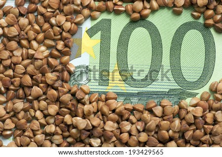 buckwheat grains on one hundred euro - stock photo