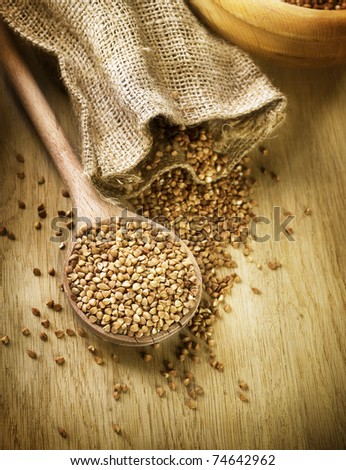 Buckwheat groats in a wooden spoon - stock photo