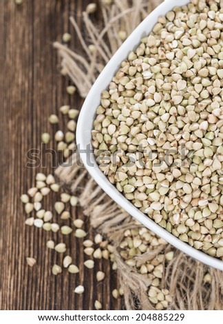 Buckwheat in a small bowl (detailed close-up shot) on dark wooden background