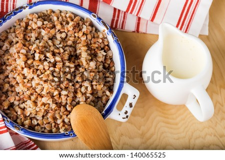 Buckwheat  in ceramic bowl  with milk for breakfast on wooden background. Selective focus. - stock photo