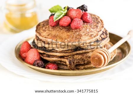 Buckwheat pancakes with berry fruit,honey and sugar powder,selective focus  - stock photo