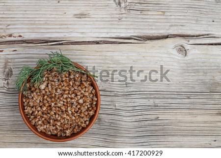Buckwheat porridge cooked with butter in an earthenware bowl on wooden gray background. Top view, closeup. - stock photo
