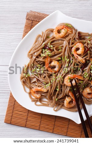 buckwheat soba noodles with shrimp on a plate close-up. vertical   - stock photo