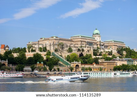 Buda Castle historic landmark and passenger boats on the Danube River in Budapest, Hungary. - stock photo