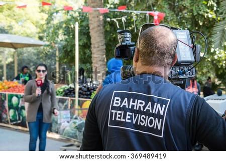 BUDAIYA, BAHRAIN - 30 JANUARY, 2016: A cameraman from Bahrain Television prepares to shoot a segment with a presenter at the weekly Farmers' Market in Budaiya Botanical Garden. - stock photo