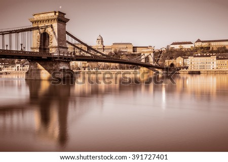 Budapest Castle and famous Chain Bridge in Budapest early morning. Focus on the bridge. This image is toned. - stock photo