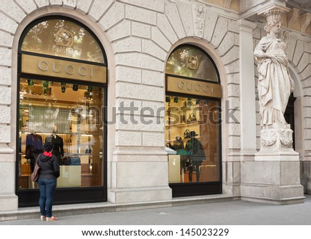 BUDAPEST - CIRCA SEPTEMBER 2012: Unidentified woman watches Gucci's window on Andrassy street, circa September 2012 in Budapest, Hungary. This fashion store opened in 2008.