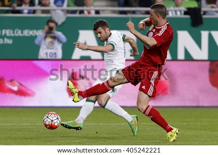 BUDAPEST, HUNGARY - APRIL 13, 2016: Gabor Gyomber of Ferencvaros (l) shots on target next to Norbert Meszaros of DVSC during Ferencvaros - DVSC Hungarian Cup semi-final soccer match at Groupama Arena