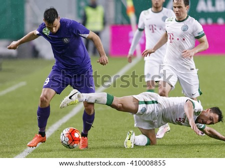BUDAPEST, HUNGARY - APRIL 23, 2016: Leandro of FTC (r) in front of Tamas Hajnal fights for the ball with Nemanja Andric of Ujpest during FTC - Ujpest OTP Bank League football match at Groupama Arena - stock photo