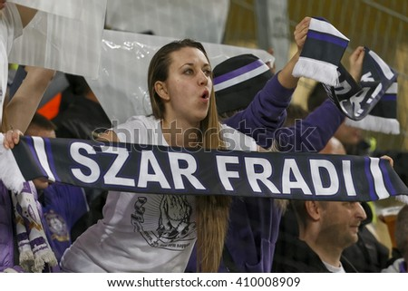 """BUDAPEST, HUNGARY - APRIL 23, 2016: Supporter of Ujpest shows a scarf with text of """"Crap Ferencvaros"""" during Ferencvaros - Ujpest OTP Bank League football match at Groupama Arena. - stock photo"""