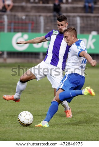 BUDAPEST, HUNGARY - AUGUST 21, 2016: David Jakab (R) of MTK crosses the ball next to Tibor Nagy (L) of Ujpest FC during the Hungarian OTP Bank Liga match between Ujpest FC and MTK at Illovszky Stadium