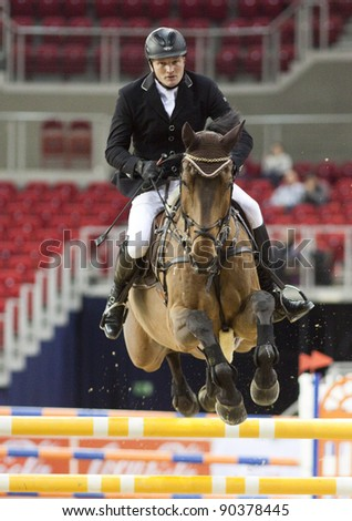 BUDAPEST, HUNGARY - DECEMBER 2: An unidentified competitor jumps with his horse at the OTP Equitation World Cup, December 2, 2011 in Budapest, Hungary - stock photo