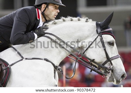 BUDAPEST, HUNGARY - DECEMBER 3: An unidentified competitor jumps with his horse at the OTP Equitation World Cup, December 3, 2011 in Budapest, Hungary - stock photo