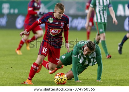 BUDAPEST, HUNGARY - FEBRUARY 10, 2016: Adam Pinter of Ferencvaros (r) is overtaken by Istvan Kovacs of Videoton during Ferencvaros - Videoton Hungarian Cup  football match at Groupama Arena.