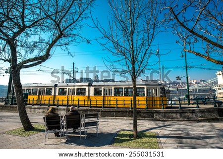 Budapest, Hungary - February 15, 2015. Two people sitting on the bench near the tram station with yellow tram on background in Budapest - stock photo