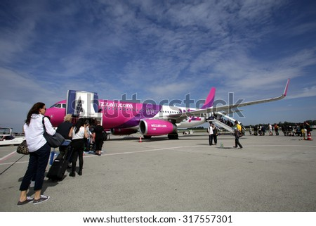 BUDAPEST, HUNGARY - FRIDAY, AUGUST 21, 2015: Passengers ready to board a WizzAir A319. WizzAir is a Central European low-cost airline.  Photographer: Mark Milstein/ Northfoto - stock photo
